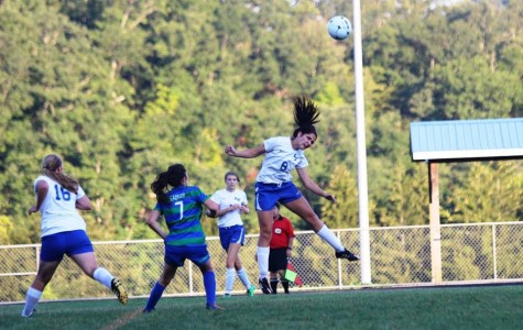 Sierra Hardy, defender, heads the ball away from the goal.