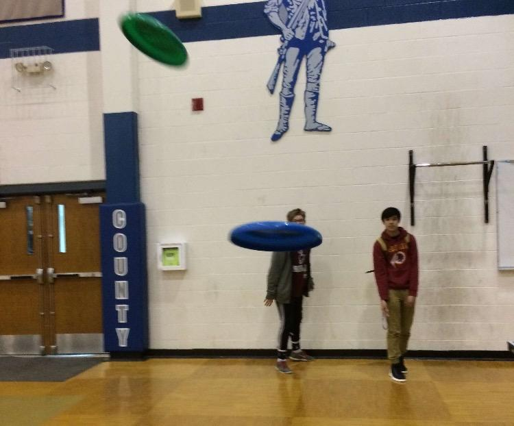 Ian Jewell and Nathann Layton practice their ultimate frisbee skills in the gym.